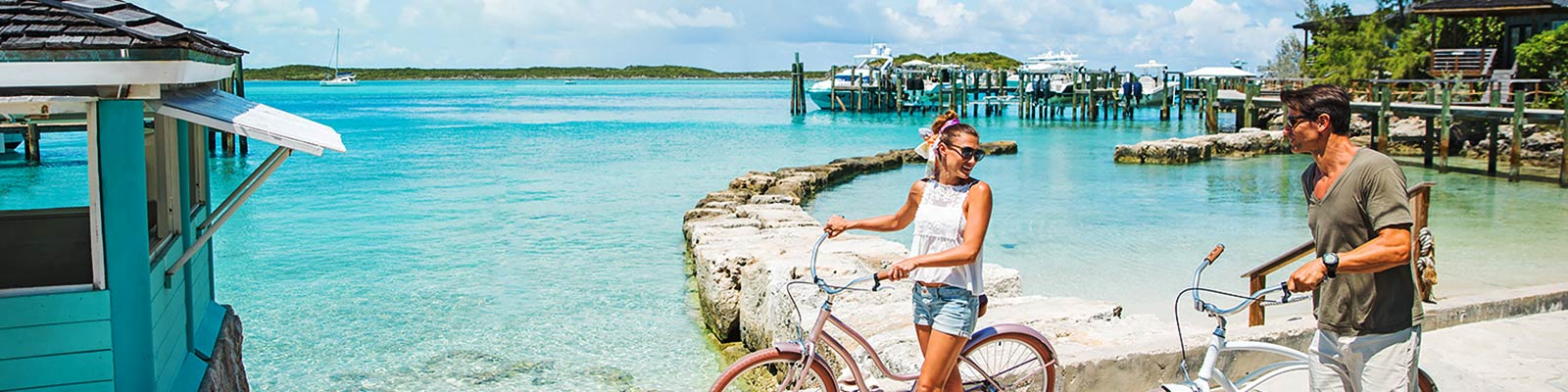 Couple pushing bicycles along wharf in Exuma Cays.