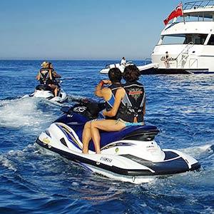 Couples returning to luxury yacht on Jet Skis